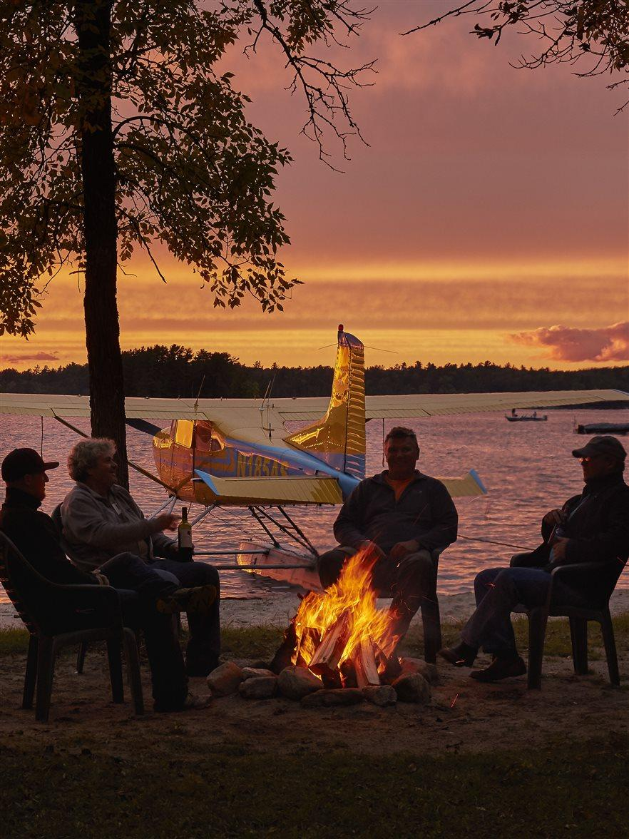 Photography of Nelsons Resort guests enjoying a fire with the Adventure Seaplanes Cessna 185 and Butch Weaver's DeHavilland Beaver beached.  Nelson's Resort Crane Lake MN USA